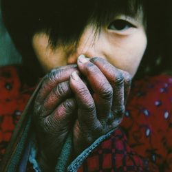 Lu-Guang-A-young-girl-warms-her-hands-in-winter.-Her-father-is-infected-with-HIV-and-still-cares-for-five-children-and-his-elderly-parents